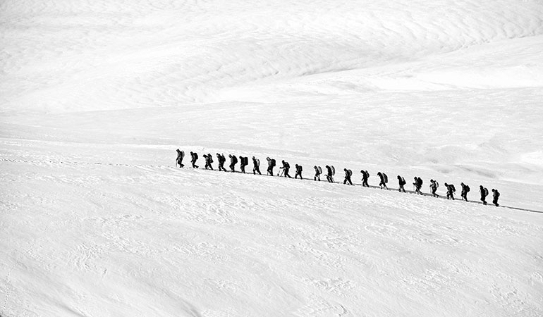 A group trekking through moon surface snow of being in private practice